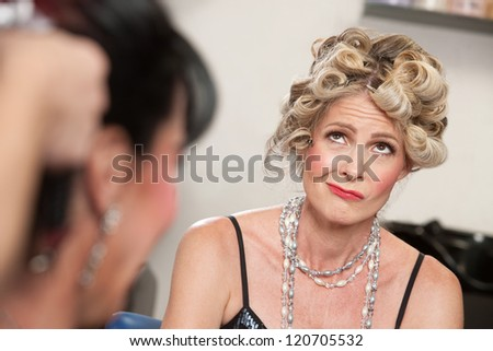Frowning European woman with friend in hair salon