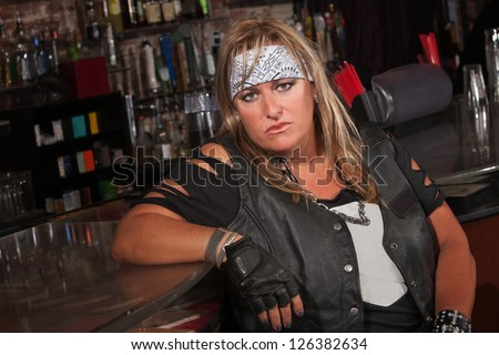 Frowning female motorcycle gang member sitting in bar