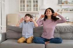 Frowning mom and son sit on couch with closed eyes and cover ears from noisy music or fight sounds from neighbors. Young female parent and kid tired of drilling noise not listen plug ears with fingers