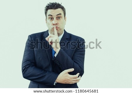 Frowning strict male boss asking to keep quiet and holding index finger near lips. Amazed businessman gesturing about silence. Secret concept #1180645681