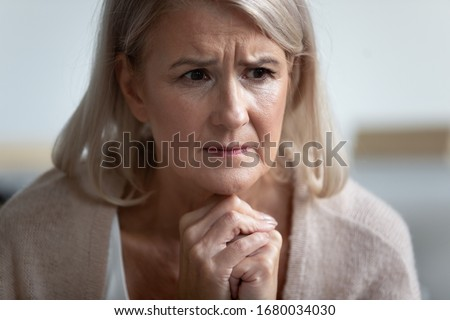 Frowning upset mature woman put head on folded hands, looking in distance. Lost in thoughts upset woman sitting alone, head shot close up portrait. Mental disorder or dementia, health problem concept.