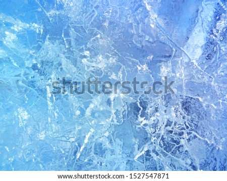 Frozen air bubbles in ice. Blue ice background.                                #1527547871