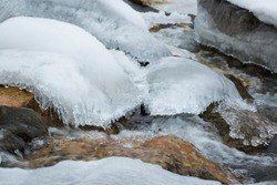 Frozen alpine river in winter in slow motion. Stones covered with frost and snow.