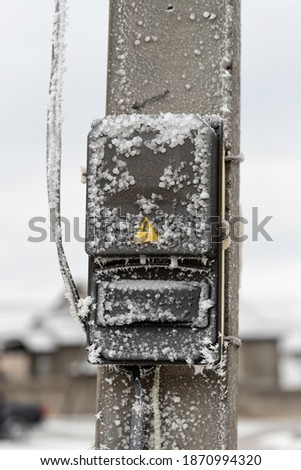 frozen and covered with ice the meter of electric energy on a concrete pillar Foto d'archivio ©