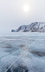 Frozen Baikal Lake on a cold February day. View from the ice to the snow-capped cliffs of Olkhon Island near Cape Khoboy. Winter holidays, ice travel. Natural background