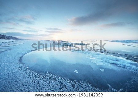 Frozen Baltic sea shore at sunset. Ice fragments close-up, snow-covered pine forest in the background. Colorful cloudscape. Symmetry reflections on the water. Nature, climate change. Panoramic view