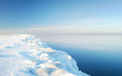 Frozen Baltic sea shore on a clear day, snow texture close-up. Blue sky. Picturesque winter scenery. Concept image. Seasons, nature, ecology, environment, climate change, global warming