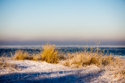 frozen beach view by the baltic sea with sand and ice in water