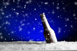 Frozen beer bottle in ice with falling snow on blue background
