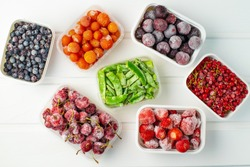 Frozen berries and vegetables in plastic boxes on white wooden background.