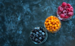 Frozen berries of raspberry, sea buckthorn and black currant in glass glasses on a dark background
