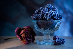 Frozen blackberry in a vase in the moonlight on a table, next to a dried rose on a table on which yellow light falls from an ajar door