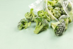 Frozen broccoli spilled out of a plastic bag. Light background with copy space. Selective focus