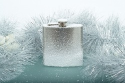 Frozen brushed metal flask on ice with snow and Christmas garland on background
