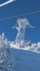 Frozen chairlift tower with frozen cable in view above