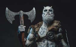 Frozen dead warrior with horns and white skin in dark armour holding two handed axe in twilight.