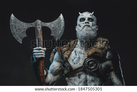 Frozen dead warrior with horns and white skin in dark armour holding two handed axe in twilight. Stock photo ©