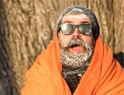Frozen excited man, bearded hipster, with beard and moustache in black sunglasses covered with white frost wrapped in orange blanket on winter day outdoors on natural background