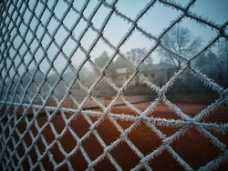 frozen fence with frost next to a tennis court on a very cold winter morning