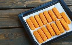 frozen fish sticks in Tray for oven on wooden background. convenience food.