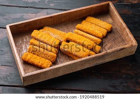 Frozen fish sticks. Organic fish food set, in wooden box, on old dark wooden table background