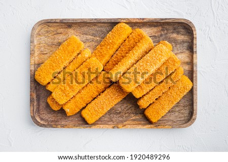 Frozen fish sticks. Organic fish food set, on wooden tray, on white background, top view flat lay