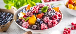 Frozen fruits blueberries blackberry raspberry red currant peach and herbs melissa.