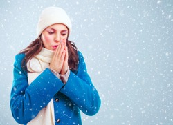 Frozen girl in blue coat, white hat and scarf heats hands among winter snowstorm.