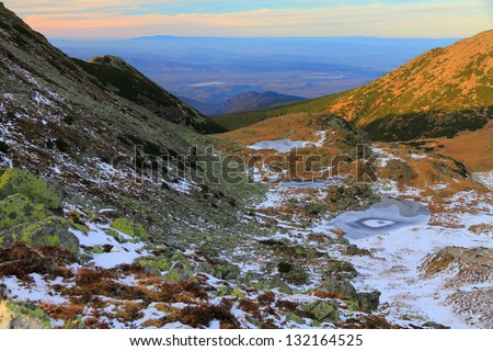Frozen glacier lake and early winter snow in the mountains, Romania