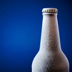 Frozen glass bottle of beer on blue.