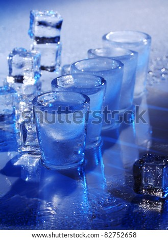 Frozen glasses and ice cubes with cold alcohol drink