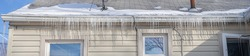 frozen gutters with long icicles hanging from ice dams panorama