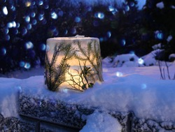 Frozen ice lantern with spruce twigs in snow, lit with candle light