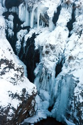 Frozen Icelandic waterfall with icicles and snow. Detail view of Hraunfossar waterfall.