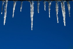 Frozen icicles hanging from a roof isolated against a blue sky background