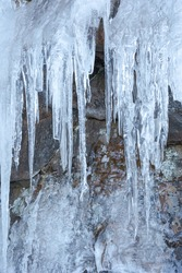 Frozen icicles on a small waterfall at Hovs hallar nature reserve in Sweden. Abstract shapes of ice hanging from mountain.