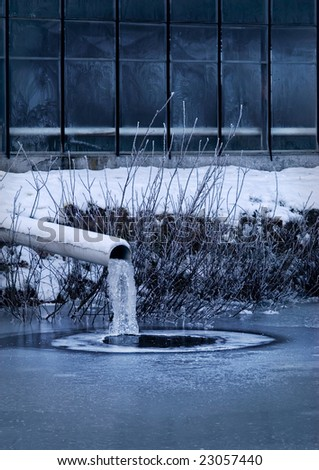 Frozen industry: frozen sewage pipe next to a factory