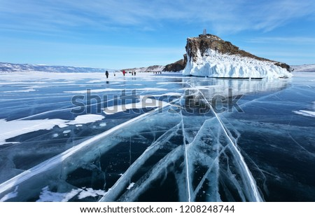 Frozen Lake Baikal. A group of tourists came on an excursion to the beautiful iced cape of Horin-Irgi or Cape Kobyliya Golova #1208248744