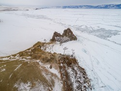 Frozen Lake Baikal, Aerial view. Beautiful winter landscape with clear smooth ice. Famous natural landmark Russia. Blue transparent ice with deep cracks, top view of a frozen lake.