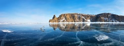 Frozen Lake Baikal. Panoramic view of beautiful mirror ice near Cape Hoboy - northern tip of Olkhon Island at sunset. Beautiful winter landscape. Natural cold background. Winter holidays, ice travel