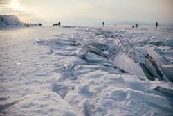 Frozen Lake Baikal. Winter landscape with beautiful smooth blue ice near rocks of Olkhon Island