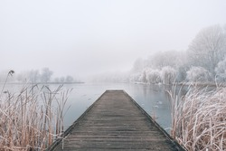 Frozen lake in winter, with wooden pier, and trees covered by snow, beautiful foggy sunset on the forest. Beautiful seasonal winter landscape, peaceful nature scenery