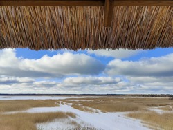 Frozen lake landscape. Marshland and dry reeds. Thatched roof part at the front of the landscape.