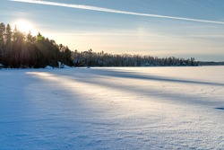 Frozen lake shore and surface covered with snow on sunset in a good weather day