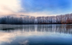 Frozen lake under a blue sky in the winter.Landscape with frozen lake.Trees in winter by the lake.