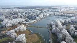 Frozen like. Aerial drone overhead flying over river ice with forest in winter.