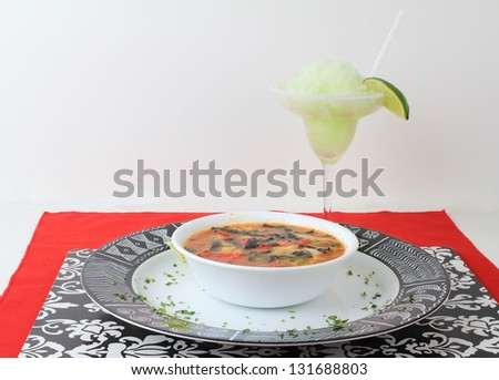 Frozen lime margarita with bowl of tortilla soup in black, red and white color scheme with Mexican Aztec graphics on platter.