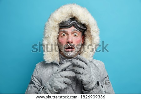 Frozen male explorer has red face covered with frost stares very shocked at camera surprised by very low temperature wears warm jacket and gloves has walk outdoor during blizzard cold weather ストックフォト ©
