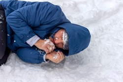 Frozen man in a blue jacket and hat lying down covered snow and frost, trying to stay warm on a very cold winter day, snow falls around him. Sick mountaineer with hypothermia on snow during the day.