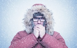 Frozen man in red winter clothes and glasses warming hands, cold, snow, frost, blizzard